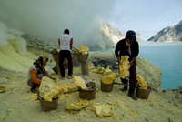 Three miners arrange their loads beside the crater lake before going up the crater path