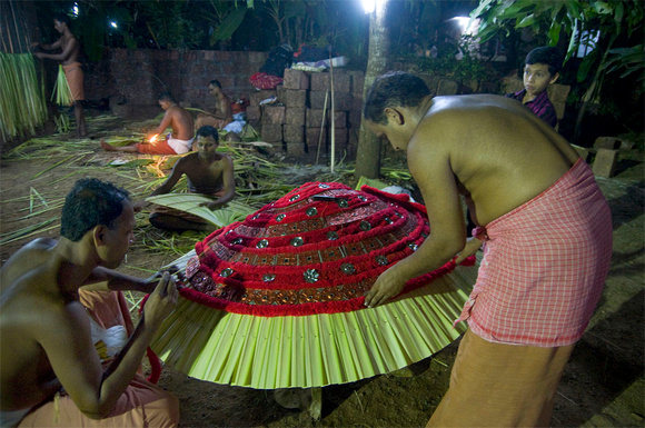 Workers preparing the god's costume using richly coloured fabrics