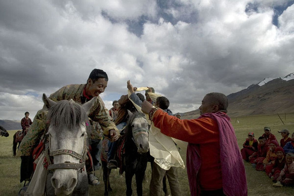 A Changpa rider is being worn the kaata, the ceremonial silk scarf by a high monk.