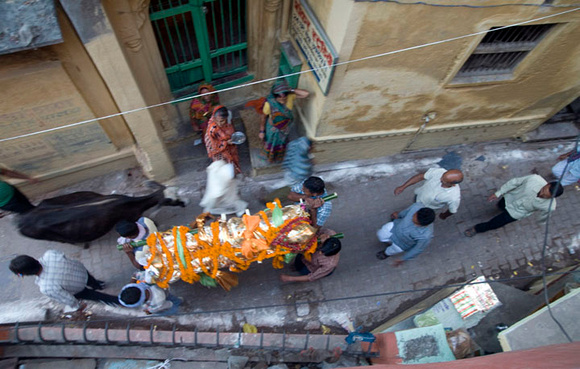 The pall bearers carrying a shrouded corpse through the serpentine lanes of Varanasi towards Manikarnika, the ghat of death.