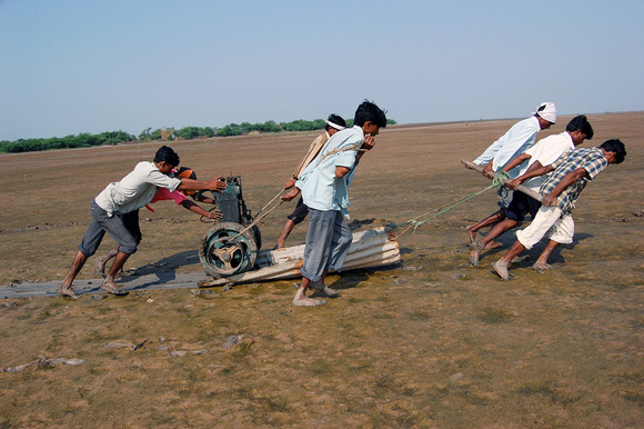 It is a herculean task to carry equipments over the marshy tract as no vehicle can negotiate the road in the post-monsoon season. Here a few workers are carrying a generator over a corrugated sheet.
