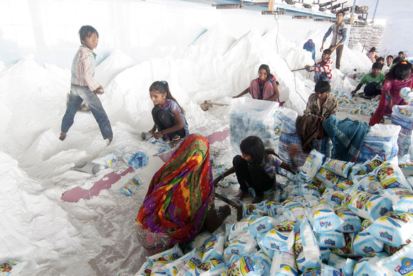 Agariya women and children working in a local salt factory. The payout for packing 1000 packets of salt is as low as INR 80 (1.19 USD).