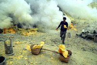 A miner runs with a block of sulphur to fill his basket