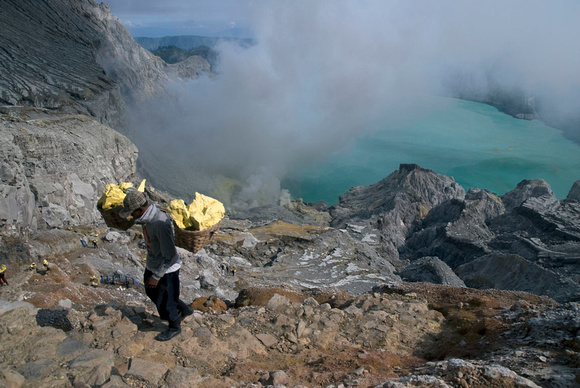 Miners carry heavy loads of sulphur weighing over 80 kg up a steep path